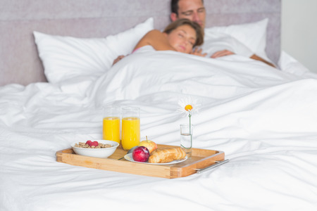 Cuddling couple asleep with breakfast tray on bed at home in bedroom photo
