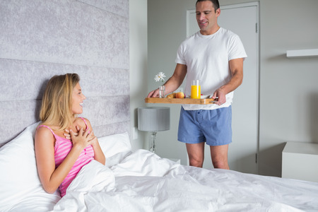spoiling: Happy woman surprised by partner bringing breakfast in bed at home in bedroom