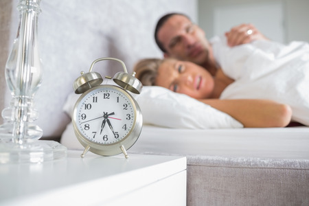 Exhausted couple looking at alarm clock  at home in bedroom photo