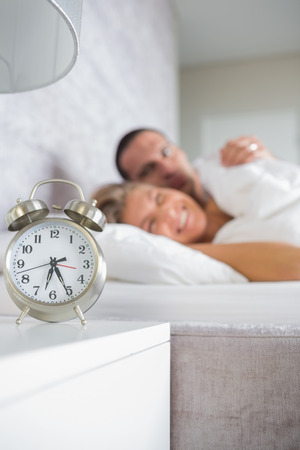 Tired couple looking at alarm clock in the morning at home in bedroom photo