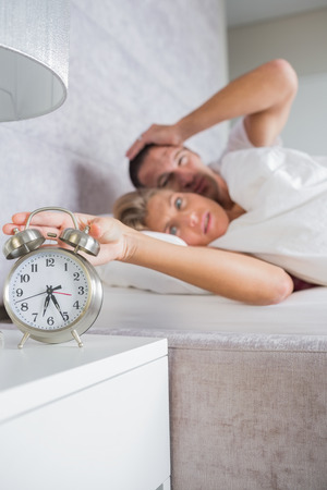 Annoyed couple looking at alarm clock in the morning with woman turning it off at home in bedroom photo