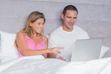 Happy young couple using their laptop together in bed at home in bedroom photo