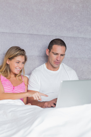 Smiling young couple using their laptop together in bed at home in bedroom photo