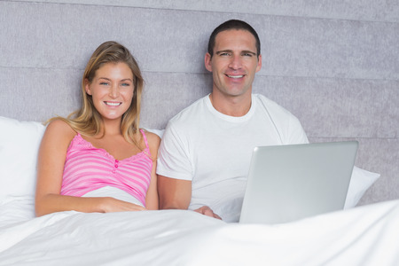 Attractive young couple using their laptop together in bed smiling at camera in bedroom at home photo