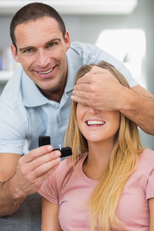 unsuspecting: Happy man about to propose to his unsuspecting girlfriend on the sofa in sitting room at home Stock Photo