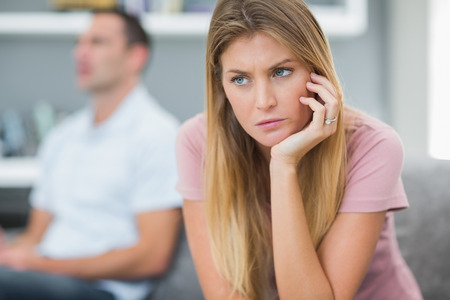 mid adult women: Sad woman thinking on couch after fight with husband in living room at home