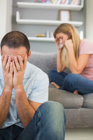 couple arguing: Young ouple having difficulties in sitting room at home Stock Photo