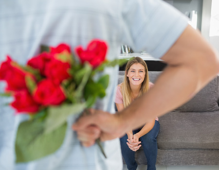 Man hiding bouquet of roses from girlfriend on the couch in sitting room at home photo