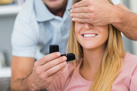 unsuspecting: Man about to propose to his unsuspecting girlfriend on the couch in sitting room at home Stock Photo
