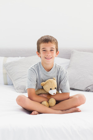 Little boy sitting on bed holding his teddy bear at home photo