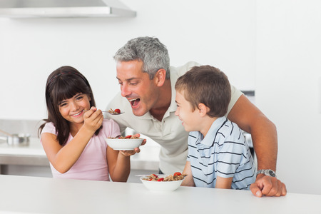 Little girl giving cereal to her father with brother smiling in kitchen photo