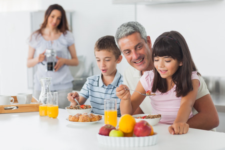 Happy family eating breakfast in kitchen together at home photo