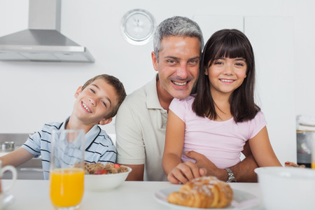 Siblings eating breakfast in kitchen together with dad at home photo