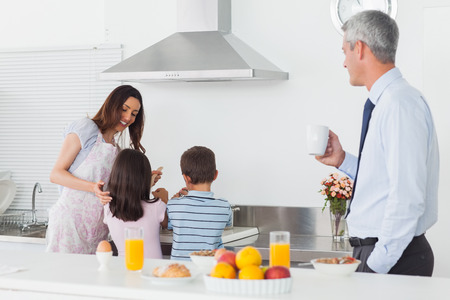 Father looking at his family cooking in the kitchen before work in the morning photo