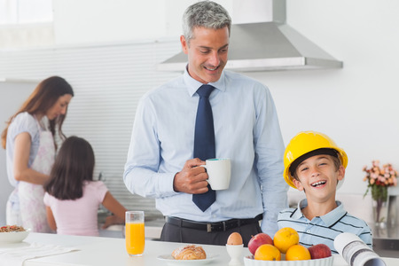 Funny little boy wearing fathers hardhat during breakfast while his mother and sister are cooking photo