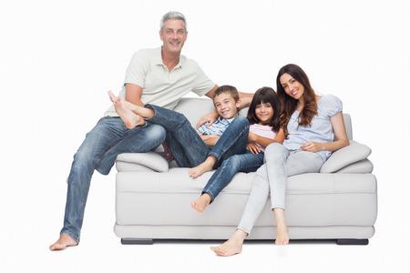 Familie zittend op de sofa glimlachen op de camera op een witte achtergrond Stockfoto