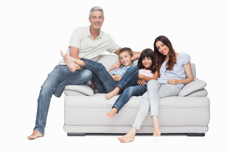 Family sitting on sofa smiling at camera on white background