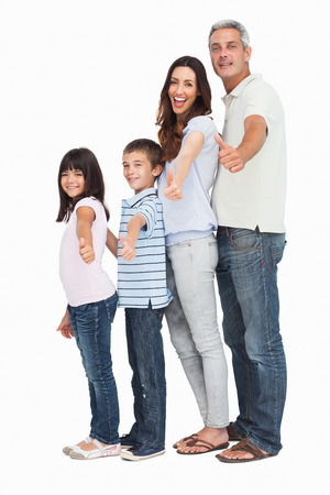 Portrait of a cute family in single file doing thumbs up at camera on white background photo