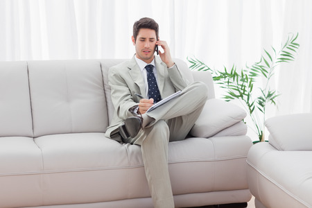 Serious businessman sitting on sofa calling with his mobile phone at office photo
