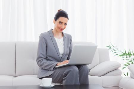 Smiling busineswoman sitting on sofa using laptop at office photo