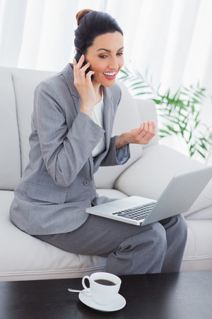 Happy businesswoman calling with her mobile phone and using laptop sitting on sofa at office photo