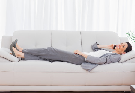 Businesswoman lying on sofa calling with her mobile phone at office photo