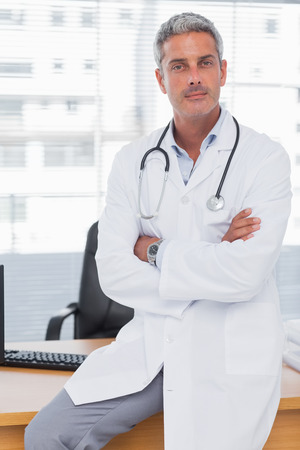 Serious doctor sitting on desk with arms crossed and looking at camera photo