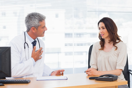 Serious patient talking with her doctor about illness in medical office photo