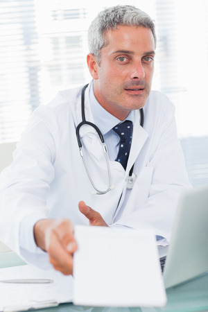 Doctor giving prescription to camera in medical office photo