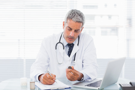Doctor holding medication and writing a prescription at medical office photo
