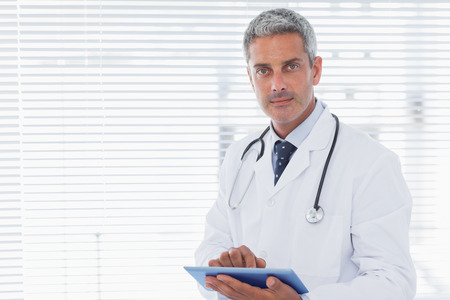Doctor holding his tablet pc and looking at camera in medical office photo