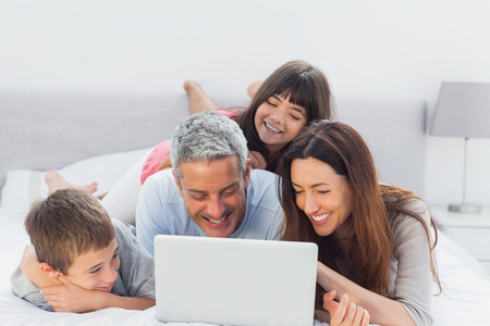 Family lying on bed using their laptop at home photo