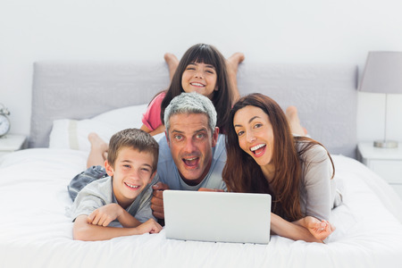 Funny family lying on bed using their laptop at home photo