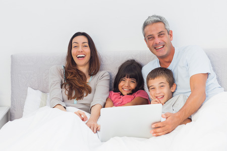 Happy family lying in bed using their laptop at home photo