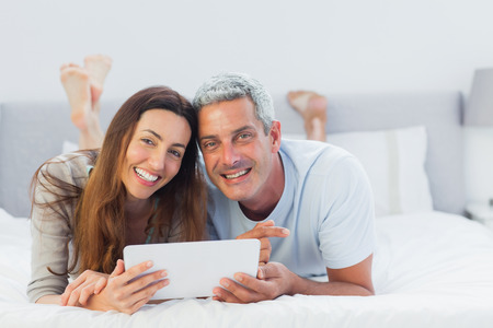 Cheerful couple lying on bed using their tablet pc in bedroom photo