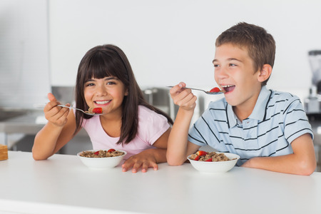 Happy siblings eating cereal for breakfast in kitchen at home photo