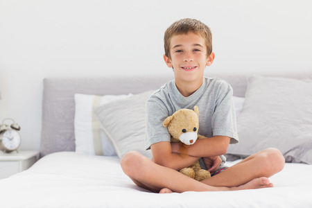 Smiling little boy sitting on bed holding his teddy bear at home photo