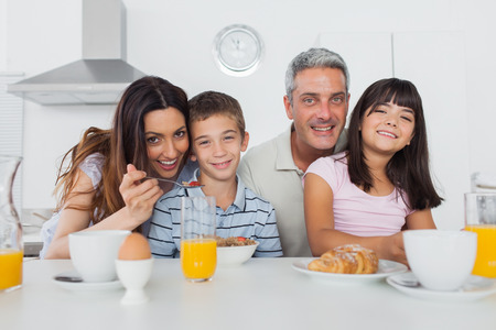 eating breakfast: Beautiful family eating breakfast in kitchen together at home