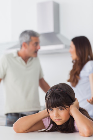 Angry couple having dispute in front of their daughter blocking her ears sitting in kitchen at home photo