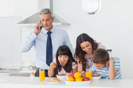 Father calling with mobile phone with his family eating breakfast in the kitchen at home photo