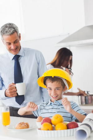 Funny little boy wearing hardhat during breakfast with his parents in the kitchen photo