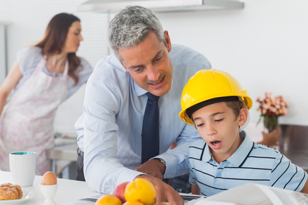 Father showing son his blueprints as he is wearing hardhat at home in kitchen before work photo