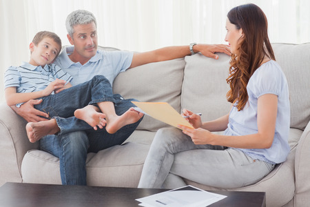Parents with their son sitting on sofa at home photo