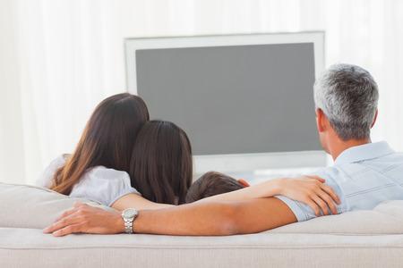 mujer viendo tv: Familia viendo la televisi�n juntos en el sof� en casa