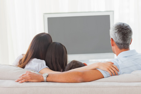 sofa television: Family watching television together on sofa at home Stock Photo