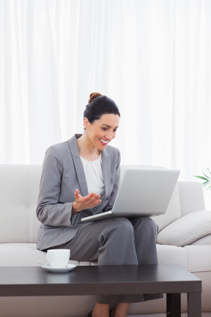 tied down: Happy busineswoman sitting on sofa using laptop at office