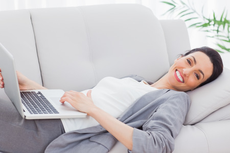 Happy businesswoman lying on sofa using laptop at office photo