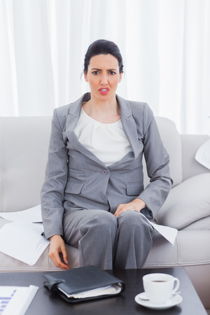 outraged: Outraged businesswoman sitting on sofa looking at camera at office