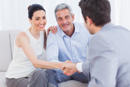 Mujer que sacude las manos con el vendedor se sienta al lado del marido en el sofá en casa