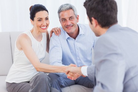Woman shaking hands with salesman sitting beside husband on couch at home Stock Photo